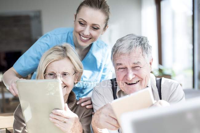Cheerful caregiver assisting senior couple using digital tablets in care home. — Stock Photo