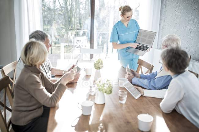 Female caregiver showing laptop to senior adults with tablets in care home. — Stock Photo