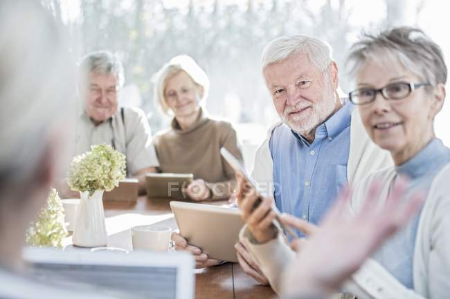 Senior adults talking in care home with tablet computers. — Stock Photo