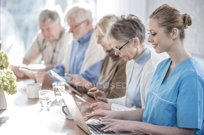Adultes âgés dans une maison de soins utilisant des ordinateurs tablettes avec travailleur de soins utilisant un ordinateur portable . — Photo de stock