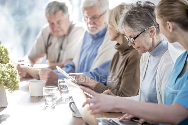 Взрослые в доме престарелых используют планшетные компьютеры с открытым ноутбуком . — стоковое фото