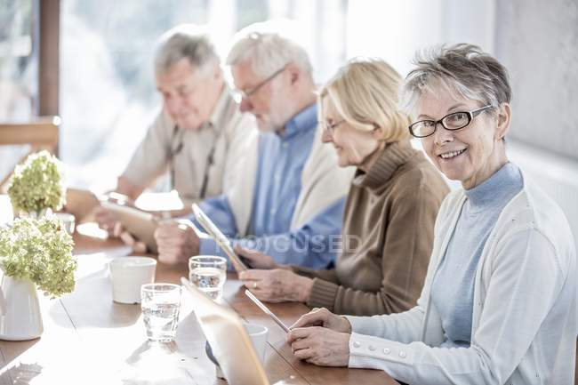 Senior adults in care home using tablet computers at table. — Stock Photo