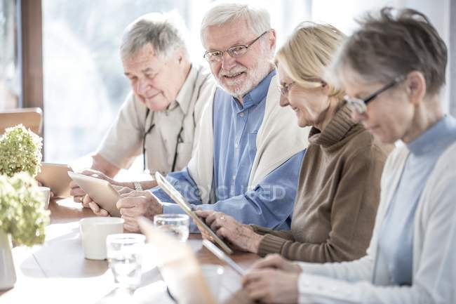 Senior adults in care home using tablet computers at table with drinks. — Stock Photo