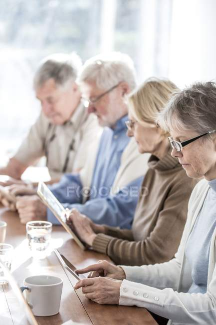 Senior adults in care home using tablet computers. — Stock Photo