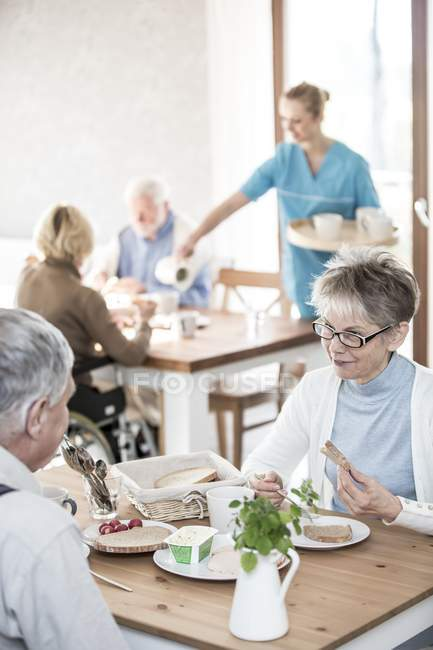 Senior adults eating breakfast in care home while caregiver serving. — Stock Photo