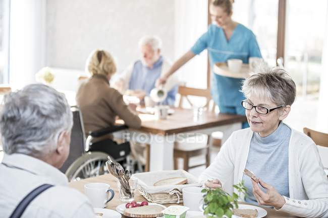 Senior adults having breakfast in care home while caregiver serving tea. — Stock Photo