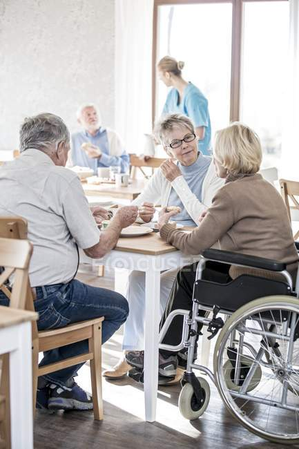 Woman in wheelchair with senior friends having breakfast in care home. — Stock Photo