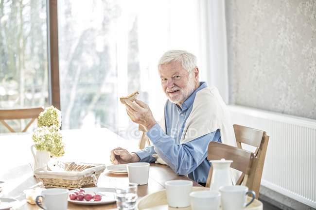 Старший мужчина завтракает за столом в доме престарелых . — стоковое фото