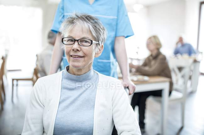 Senior women smiling and looking in camera with nurse in care home. — Stock Photo