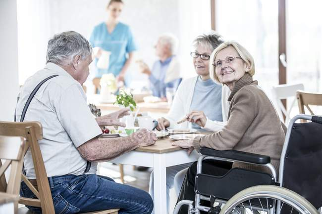 Senior adults dining in care home while woman in wheelchair looking in camera. — Stock Photo