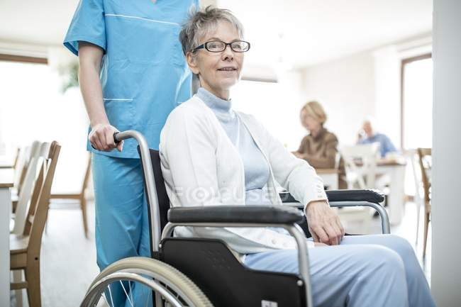 Nurse pushing senior woman in wheelchair in care home. — Stock Photo
