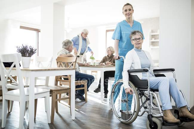 Senior woman in wheelchair posing with care worker in care home. — Stock Photo