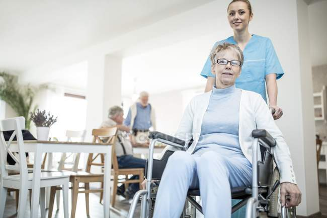 Senior woman in wheelchair with female nurse in care home. — Stock Photo