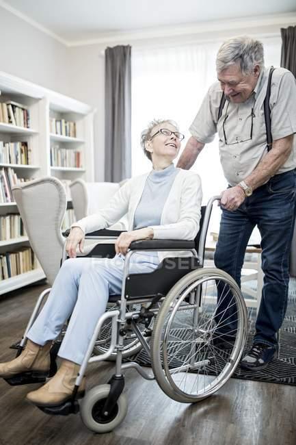 Senior mulher em cadeira de rodas olhando para o homem sênior e sorrindo . — Fotografia de Stock