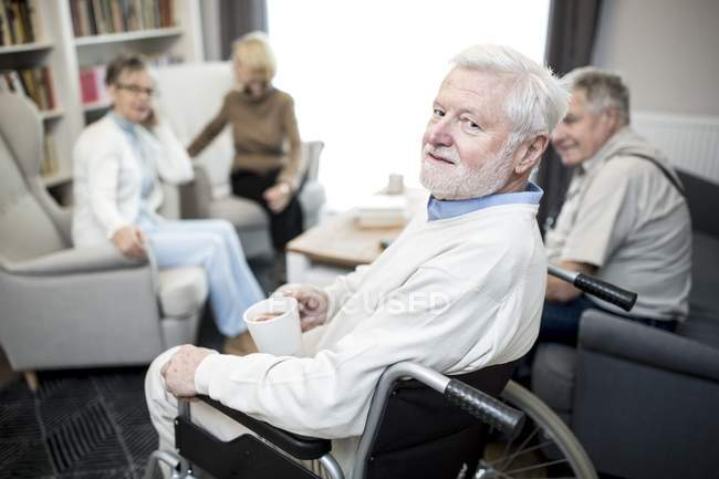 Senior man in wheelchair holding teacup and looking in camera with friends in care home. — Stock Photo