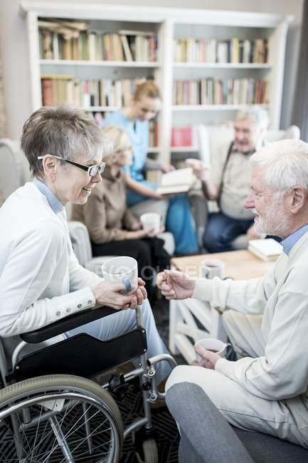 Senior mulher em cadeira de rodas falando com amigo masculino na sala de estar do lar de cuidados . — Fotografia de Stock