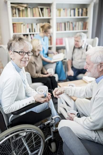 Seniorin mit Tasse im Rollstuhl sitzt mit männlichen Freunden und Krankenschwester im Pflegeheim. — Stockfoto