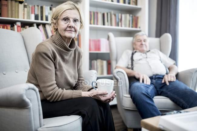 Старшая пара, сидящая в креслах в гостиной . — стоковое фото