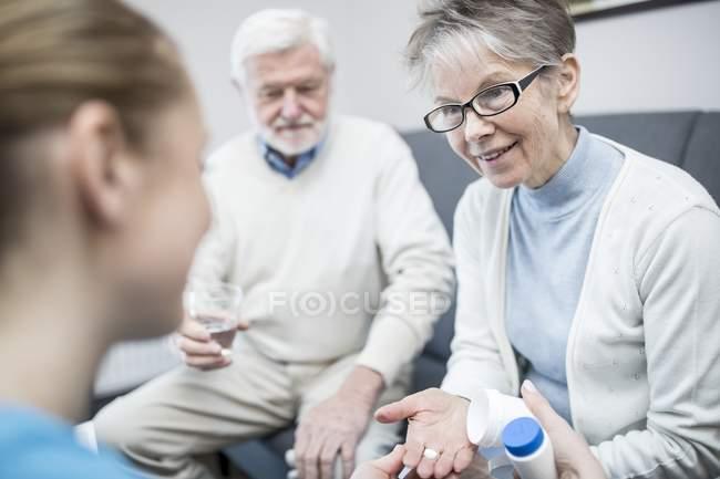 Senior couple receiving prescription medication from nurse in care home. — Stock Photo