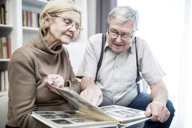 Старшая пара вместе рассматривает фотоальбом . — стоковое фото