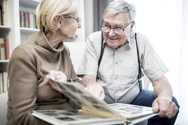 Senior couple looking at each other and smiling with photo album. — Stock Photo