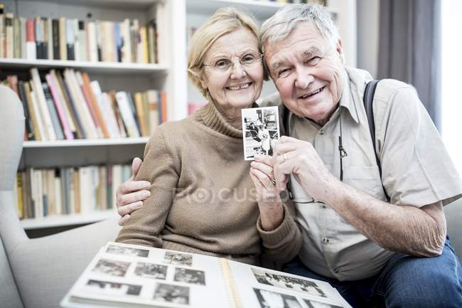 Senior couple posing with photograph from photo album. — Stock Photo