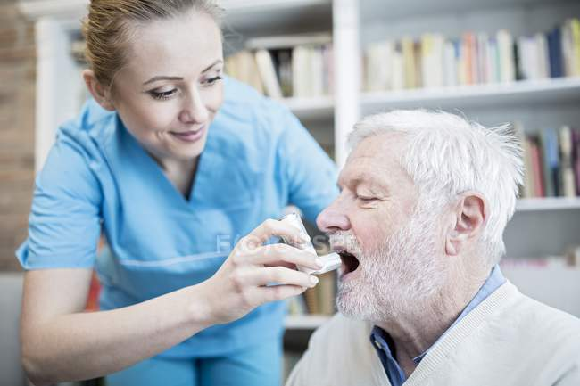 Care worker helping senior man with inhaler. — Stock Photo