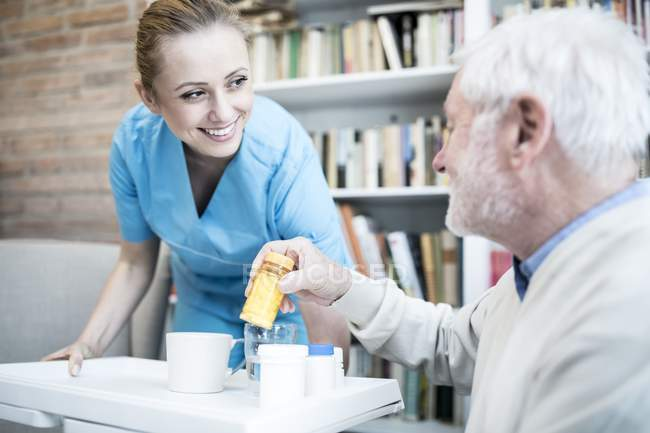 Nurse bending and holding tray with medicine bottles for senior man in care home. — Stock Photo
