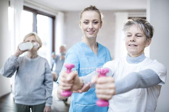 Female physiotherapist helping senior woman holding hand weights with woman drinking in background. — Stock Photo