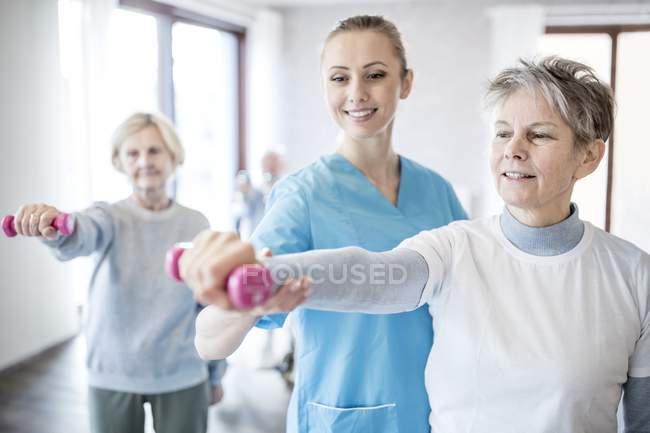 Senior woman holding hand weight with physiotherapist helping. — Stock Photo