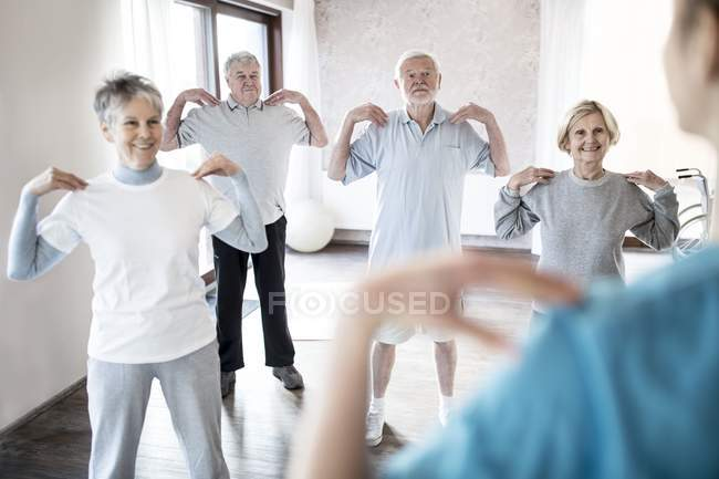 Senior adults exercising in physiotherapy class with nurse. — Stock Photo
