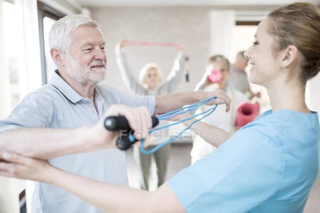 Seniorchef mit Widerstandsband im Training mit Physiotherapeut. — Stockfoto