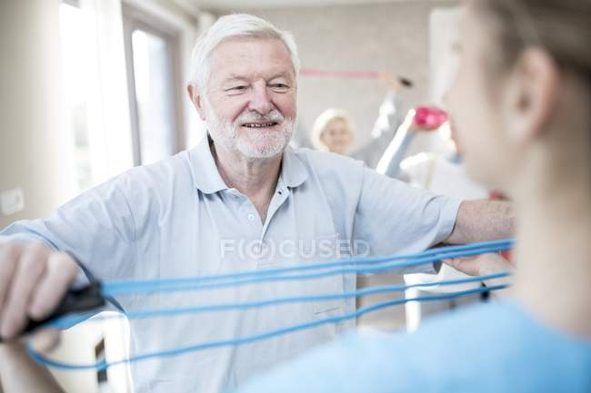 Senior man using resistance band in exercise class with worker. — Stock Photo