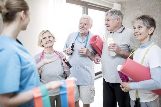 Старшие взрослые держат спортивный инвентарь с физиотерапевтом на занятиях . — стоковое фото