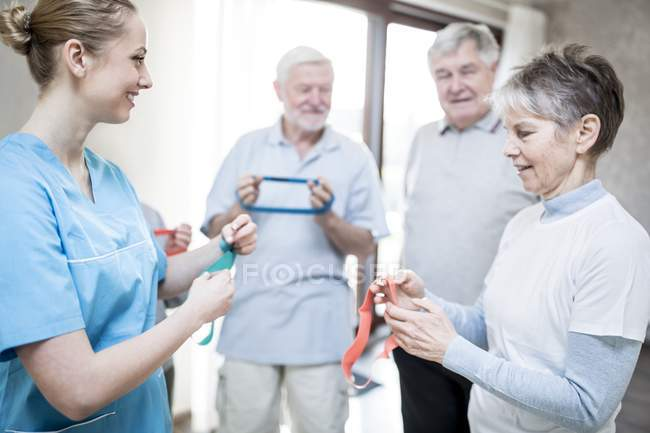 Senior adults holding resistance bands with physiotherapist in exercise class. — Stock Photo