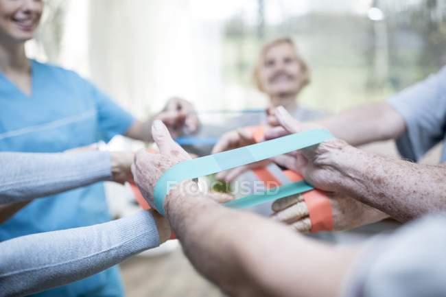 Крупный план рук пожилых людей с использованием полос сопротивления в упражнениях класса . — стоковое фото