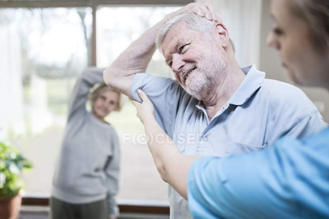 Senior man stretching in class with physiotherapist helping. — Stock Photo