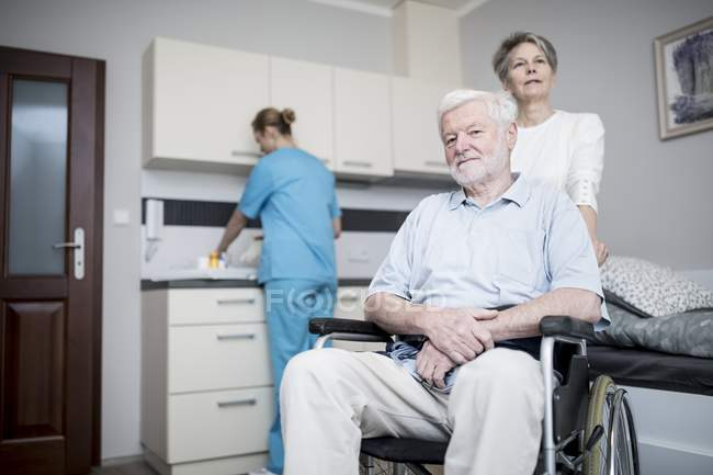 Senior man sitting in wheelchair with women in care home. — Stock Photo