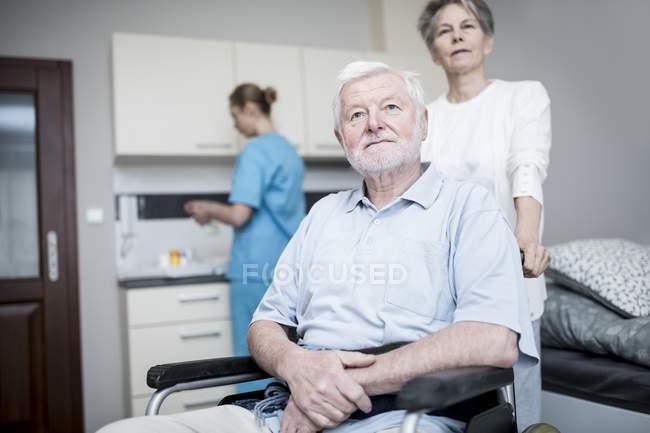 Senior im Rollstuhl posiert mit Frauen in Pflegeheim. — Stockfoto