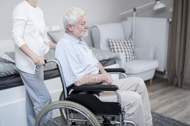 Senior woman pushing senior man in wheelchair in care home. — Stock Photo