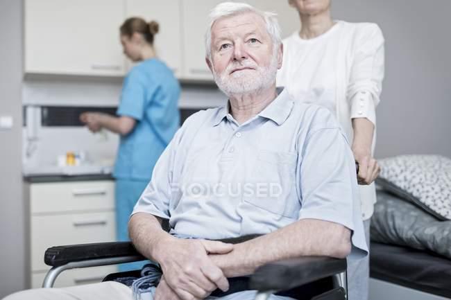 Senior sitzt im Rollstuhl und schaut im Pflegeheim auf. — Stockfoto