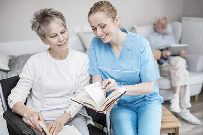 Caregiver reading book with senior woman with senior man using tablet in background in care home. — Stock Photo