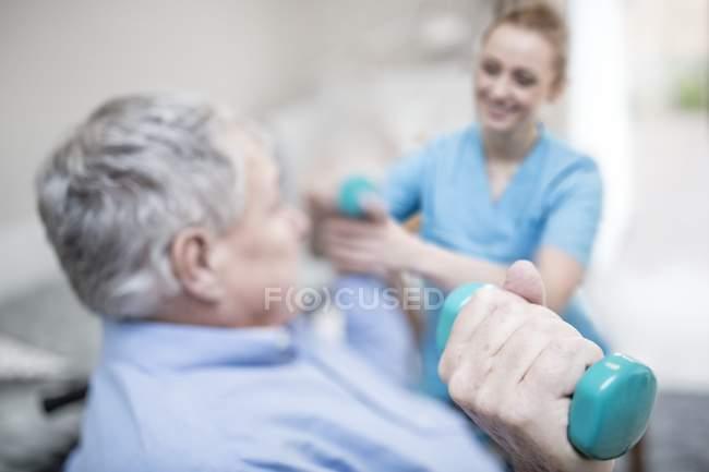 Физиотерапевт помогает пожилому человеку поднимать тяжести рук . — стоковое фото