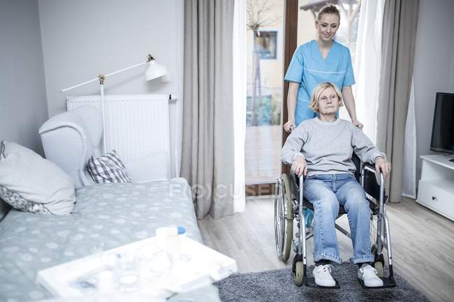 Female nurse pushing senior woman in wheelchair in care home. — Stock Photo