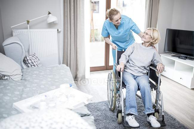 Senior woman in wheelchair talking with care worker in care home. — Stock Photo
