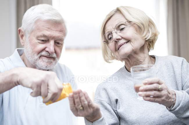 Senior man giving senior woman with glass of water medication. — Stock Photo