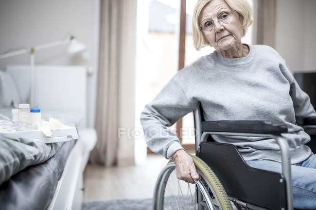 Mulher idosa em cadeira de rodas por cama com medicação em casa de repouso . — Fotografia de Stock