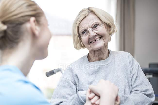Femme Senior souriant à l'éducateur. — Photo de stock