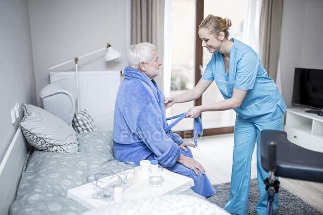 Cuidador ayudando a hombre mayor a ponerse la bata . - foto de stock