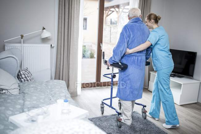 Care worker helping senior man walking with rollator. — Stock Photo